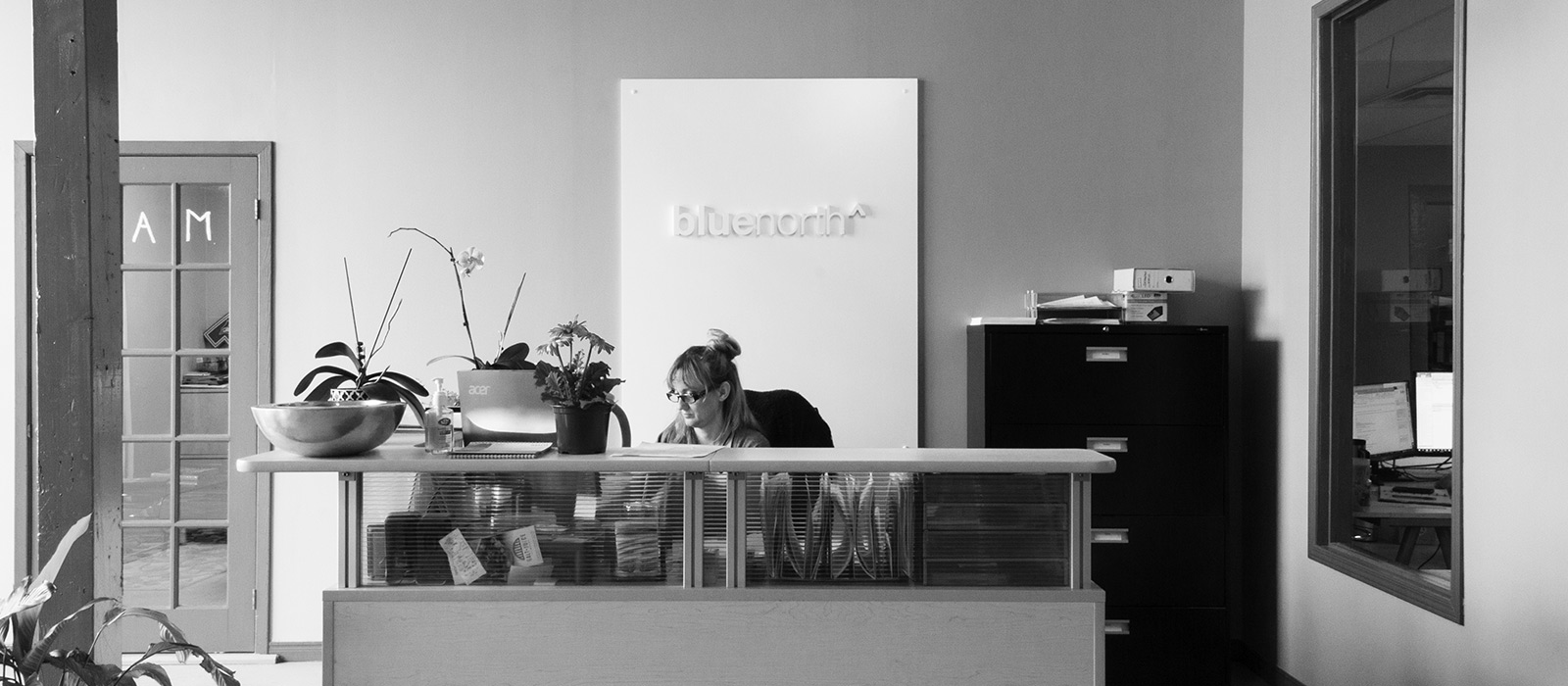 Blue North Receptionist sitting at her desk
